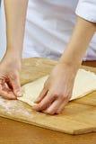Frau rollt Pressungsteig handgemachte Reihen-Lebensmittelrezepte Stockfoto