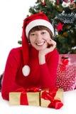 Frau in rotem Sankt-Hut, der unter Weihnachtsbaum mit Geschenken liegt Lizenzfreies Stockbild