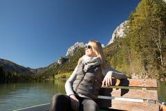 Frau rudert mit einem Ruderboot mit einem See in den Bergen Lizenzfreie Stockfotografie