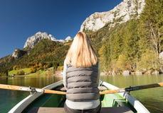 Frau rudert mit einem Ruderboot mit einem See in den Bergen Stockfoto
