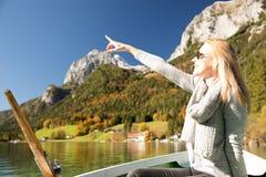 Frau rudert mit einem Ruderboot mit einem See in den Bergen Lizenzfreies Stockbild