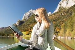 Frau rudert mit einem Ruderboot mit einem See in den Bergen Stockbilder
