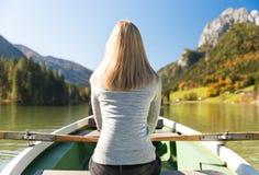 Frau rudert mit einem Ruderboot mit einem See in den Bergen Lizenzfreies Stockfoto