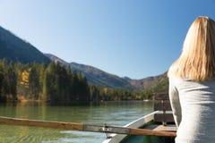 Frau rudert mit einem Ruderboot mit einem See in den Bergen Stockbild