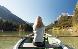 Frau rudert mit einem Ruderboot mit einem See in den Bergen Stockfotos