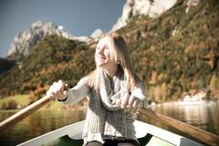 Frau rudert mit einem Ruderboot mit einem See in den Bergen Lizenzfreie Stockfotos