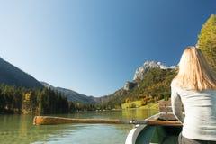 Frau rudert mit einem Ruderboot mit einem See in den Bergen Stockfotografie