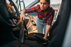 Frau säubert Autoinnenraum mit Staubsauger stockfotos
