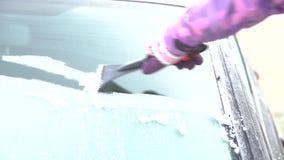 Frau säubert das Autofenster vom Schnee und Eis mit einem Schaber stock video footage