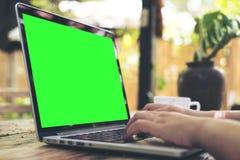 Frau ` s übergibt das Arbeiten und das Schreiben an Laptop mit leerem grünem Schirm auf Holztisch mit grünem Naturhintergrund Stockfoto