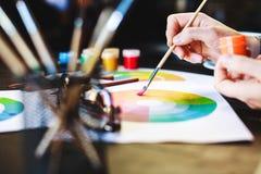 Frau ` s übergibt das Halten der Farbe, der Bleistifte und der Zeichnungen auf Tabelle Lizenzfreie Stockbilder