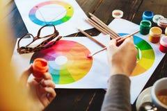 Frau ` s übergibt das Halten der Farbe, der Bleistifte und der Zeichnungen auf Tabelle Stockfotografie