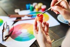 Frau ` s übergibt das Halten der Farbe, der Bleistifte und der Zeichnungen auf Tabelle Lizenzfreie Stockfotografie