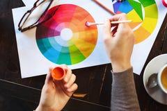 Frau ` s übergibt das Halten der Farbe, der Bleistifte und der Zeichnungen auf Tabelle Stockbilder