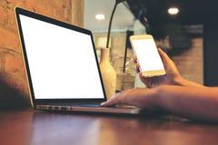 Frau ` s übergibt das Halten des Handys bei der Anwendung des Laptops mit leerem weißem Schirm auf Weinleseholztisch im Dachboden Lizenzfreies Stockbild