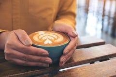 Frau ` s übergibt das Halten einer blauen Schale heißen Lattekaffees mit Lattekunst auf hölzerner Weinlesetabelle lizenzfreies stockfoto