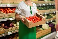 Frau ` s übergibt das Halten eines großen Kastens der Tomatenernte im Markt stockbilder