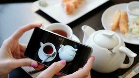 Frau ` s übergibt die Blätterbildung durch Fotos von Tassen Tee und Teekanne auf dem Schirm des Handys Lizenzfreie Stockbilder