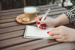 Frau ` s übergibt Schreiben auf Notizbuch, heißem Kaffee und Weinlese woode lizenzfreies stockbild