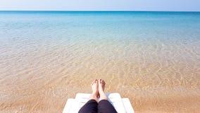 Frau ` s Bein legen auf den weißen Lehnsessel auf dem Strand Lizenzfreie Stockfotografie