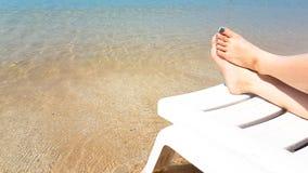Frau ` s Bein legen auf den weißen Lehnsessel auf dem Strand Lizenzfreies Stockfoto