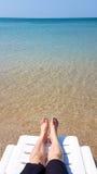 Frau ` s Bein legen auf den weißen Lehnsessel auf dem Strand Lizenzfreie Stockfotos