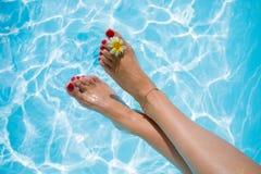Frau ` s Beine über dem Swimmingpool Lizenzfreie Stockbilder