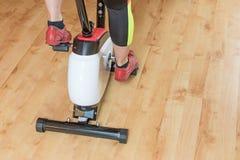 Frau ` s Beine, die auf der Hometrainernahaufnahme ausbilden Stockfotografie