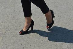 Frau ` s Beine mit den roten Nägeln poliert in den schwarzen Sandalen lizenzfreies stockfoto