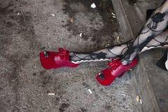 Frau ` s Beine mit rotem ledernem Pfennigabsatz Stockfoto