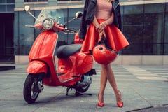 Frau ` s Beine nähern sich rotem Roller Stockfotografie