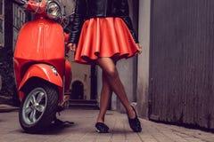 Frau ` s Beine nähern sich rotem Roller Stockbilder