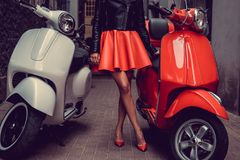 Frau ` s Beine zwischen zwei Rollern Lizenzfreie Stockfotos