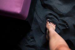 Frau ` s Füße auf schwarzem Sand von oben lizenzfreie stockfotos