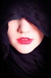 Frau \ 's-Gesicht mit schwarzer Haube Stockfotografie