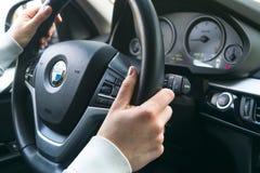 Frau ` s Hände auf einem Lenkrad, das BMW X5 F15 fährt Hände, die Lenkrad halten moderne Autoinnenraumdetails Stockfoto