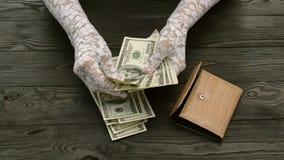 Frau ` s Hände, in den weißen Spitzehandschuhen, zählen die US-Dollars Banknoten vom braunen ledernen Geldbeutel stock footage
