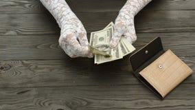 Frau ` s Hände, in den weißen Spitzehandschuhen, zählen die US-Dollars Banknoten von einem braunen ledernen Geldbeutel stock footage