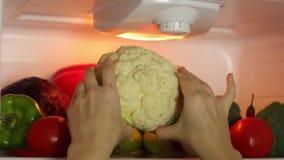 Frau ` s Hände erhalten Blumenkohl vom Kühlschrank stock video