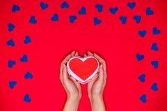 Frau ` s Hände halten rotes Herz auf rotem Hintergrund lizenzfreies stockbild