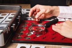 Frau ` s Hände mit einer Münze und einem Kasten Münzen Lizenzfreies Stockbild