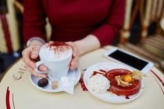 Frau ` s Hände mit Handy, Tasse Kaffee und Kuchen Stockfoto