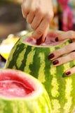 Frau ` s Hände mit Wassermelonen eines Messerausschnitts auf dem Picknick draußen Lizenzfreie Stockfotos