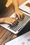Frau ` s Hand, die auf Laptop schreibt Stockbild