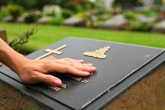 Frau ` s Hand, die das schwarze Steingrab berührt Traurigkeitsmoment Lizenzfreie Stockfotos