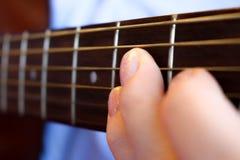 Frau ` s Hand, die eine Gitarre spielt Lizenzfreies Stockfoto