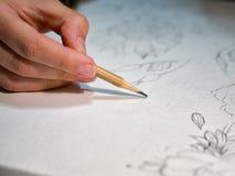 Frau ` s Hand, die einen Bleistift und ein Zeichnen Blumen auf watercolo hält Stockfotos