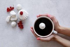 Frau ` s Hand, die einen Tasse Kaffee auf einem weißen Hintergrund hält stockbild