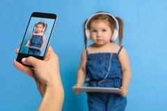 Frau ` s Hand, die Foto von einem kleinen Mädchen mit einem Handy macht Selektiver Fokus an einem Handy mit einem Porträt von a Stockbild
