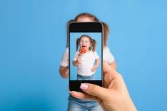 Frau ` s Hand, die Foto von einem kleinen Mädchen mit einem Handy macht Selektiver Fokus an einem Handy mit einem Porträt von a Lizenzfreie Stockfotos